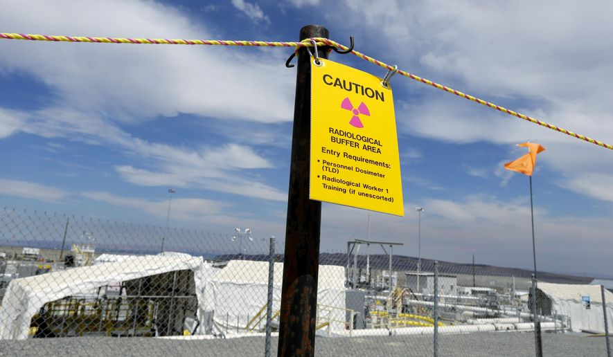 "A sign warns of radioactivity near a wind direction flag indicator at the ""C"" tank farm during a media tour of the Hanford Nuclear Reservation Wednesday, July 9, 2014 near Richland, Wash. Officials said Wednesday that 12,000 air samples taken at Hanford this year after more than three dozen workers reported being sickened by chemical vapors have failed to find a cause for the problem. (AP Photo/Ted S. Warren)"