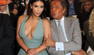 Kim Kardashian and fashion designer Valentino pose for photographers prior to the presentation of the Valentino Fall Winter 2014-15 Haute Couture fashion collection designed by Italian creative directors Maria Grazia Chiuri and Pierpaolo Piccioli, in Paris, Wednesday, July 9, 2014. (AP Photo/Francois Mori)