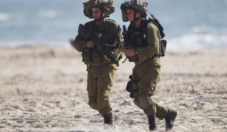Israeli soldiers patrol along the beach front near the Israel-Gaza Border, Wednesday, July 9, 2014. Israel stepped up its offensive on the Hamas-run Gaza Strip on Wednesday, pummeling scores of targets and killing more than a dozen people as Israeli leaders signaled a weeks-long ground invasion could be quickly approaching. (AP Photo/Ariel Schalit)