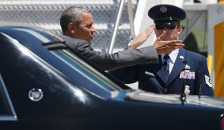 President Barack Obama gestures to reporters on the tarmac before boarding Air Force One at Denver International Airport, Wednesday, July 9, 2014, en route to Dallas, where he is expected to attend a meeting on immigration.  (AP Photo/David Zalubowski)