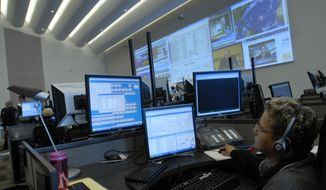 Velda Norris, from Largo Md., a telecommunications operator for the past six years, fields 911 emergency and 311 non emergency phone calls during the grand opening of the Unified Communications Center.  The state of the art communications center will facilitate the coordination of local and regional first responders and emergency preparedness teams, located in Ward 8 of Southeast  Washington.  Tuesday September 26,  2006  ( Nancy Pastor / The Washington Times )