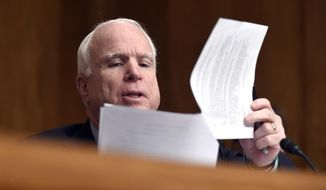 ** FILE ** Sen. John McCain, R-Ariz., reads the restrictions for visitors to immigration centers during a Senate Homeland Security and Governmental Affairs Committee hearing on Capitol Hill in Washington, Wednesday, July 9, 2014. (AP Photo/Susan Walsh)