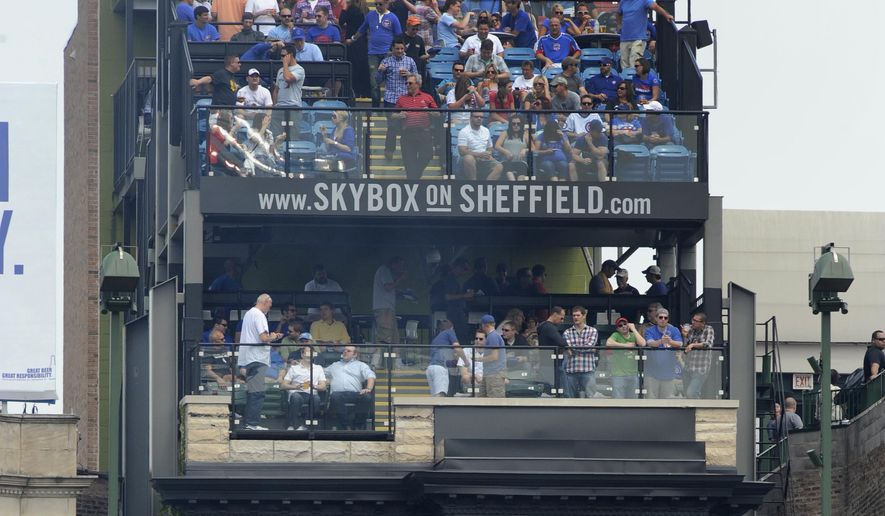 Baseball fans watch a Chicago Cubs game from a rooftop across from Wrigley Field's right-field bleachers in Chicago on June 8, 2013. (Associated Press) **FILE**