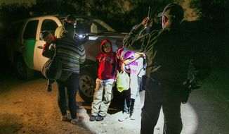 Women from Honduras traveling with their children are stopped by U.S. Customs and Border Protection Services agents after crossing the Rio Grande near McAllen, Texas. About 90 Hondurans a day cross illegally into the U.S. from Mexico. (associated press)