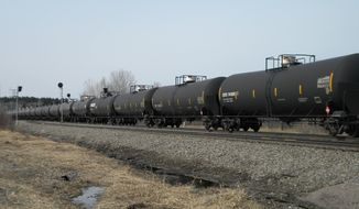 FILE - In this April 15, 2014  file photo, an oil-tank train with crude oil from the Bakken shale fields of North Dakota  travels near Staples, Minn. The University of Minnesota releases a new study on financial losses for farmers due to rail delays in shipping agriculture  commodities, blaming the vast quantities of oil leaving North Dakota for squeezing out other rail traffic. (AP Photo/Mike Cronin,File)