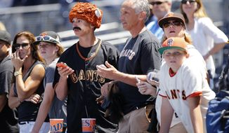 **FILE** San Francisco Giants fans watch their team take batting practice before a baseball game against the San Diego Padres in San Diego on July 4, 2014. (Associated Press)