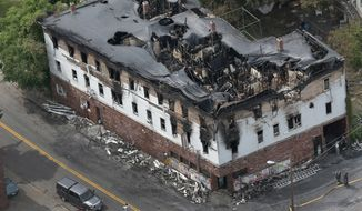 Firefighters work on the scene of a fatal fire at an apartment building in Lowell, Mass., Thursday, July 10, 2014. (AP Photo/The Boston Globe, David L Ryan)