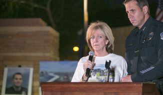 ** FILE ** This Tuesday May 3, 2014, photo shows Mesa Police Department Assistant Chief Heston Silbert  standing with Mary Ann Mendoza, mother of officer Brandon Mendoza, during a vigil for her son at Mesa Police Headquarters in Mesa, Ariz. (AP Photo/The Republic, Michael Schennum)