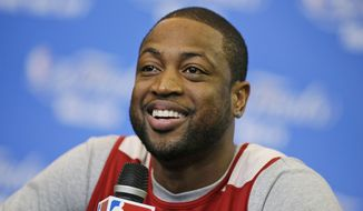 FILe - In this June 14, 2014 file photo, Miami Heat guard Dwyane Wade smiles as he is asked a question during a media availability for the NBA basketball finals in San Antonio. Signing day has arrived in the NBA, if the biggest free agents care to grab their pens. But it's unclear if Carmelo Anthony, Chris Bosh and Dwyane Wade _ who all might be waiting on LeBron James to go first _ are ready. (AP Photo/Tony Gutierrez, File)