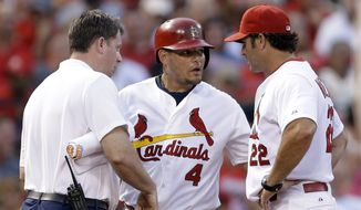 St. Louis Cardinals' Yadier Molina, center, is checked on by manager Mike Matheny, right, and trainer Chris Conroy after injuring his hand while sliding into third during the second inning of a baseball game against the Pittsburgh Pirates Wednesday, July 9, 2014, in St. Louis. Molina finished the inning but was replaced in the third inning by Tony Cruz. (AP Photo/Jeff Roberson)