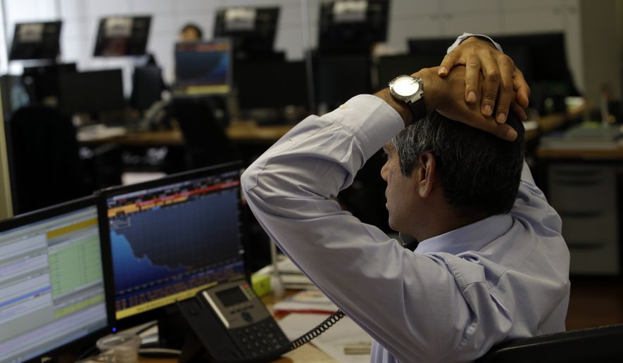 A broker stretches as he talks on the phone in a trading room of a Portuguese bank in Lisbon, Thursday, July 10, 2014. Share prices on the Lisbon stock exchange fell more than 4 percent and Portugal's bond yields ticked higher amid growing concern about the health of one of the country's largest financial groups. (AP Photo/Francisco Seco)