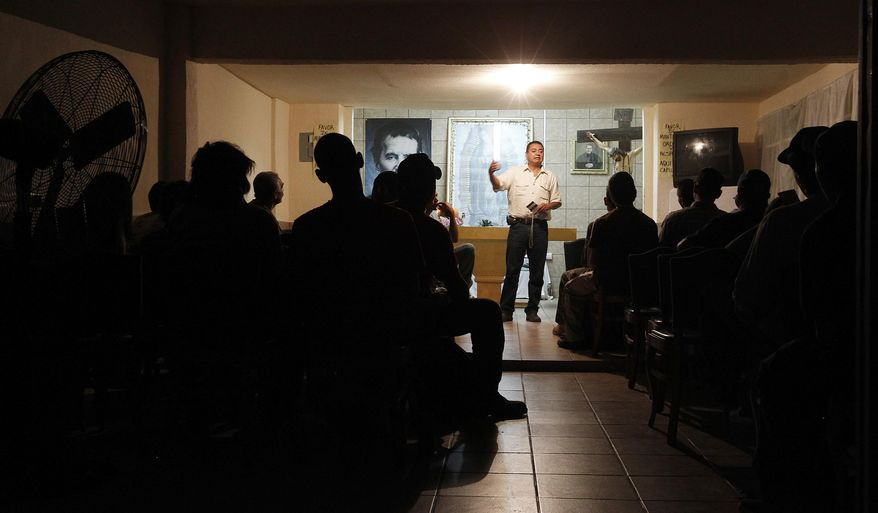 FILE - In this Aug. 9, 2012 file photo, dozens of immigrants, many of them Mexican citizens, listen to a briefing of sorts as they find out how difficult and dangerous it is to cross the border into the United States, at a well known immigrant shelter in Nogales, Mexico. A major U.S. effort to discourage repeated attempts by immigrants to enter the country illegally by flying and busing them into Mexico hundreds of miles away from where they were caught, but government statistics and interviews with migrants in Mexican shelters suggest the dislocation is rarely a deterrent, especially for immigrants with spouses, children and roots in the U.S. (AP Photo/Ross D. Franklin, File)