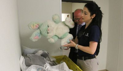 Barbara Gonzalez, public information officer for Immigration and Customs Enforcement, shows donated stuffed animals in an area where immigrant families are housed at the Artesia Residential Detention Facility inside the Federal Law Enforcement Center in Artesia, New Mexico. (AP Photo/Pool, El Paso Times, Rudy Gutierrez)