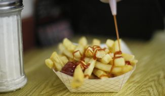 In this photo made Thursday, June 26, 2014, a customer douses her french fries with ketchup at the concession stand before the start of the movies at the Saco Drive-In in Saco, Maine. (AP Photo/Robert F. Bukaty) ** FILE **