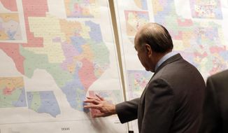 """FILE - In this May 30, 2013 file photo, Texas state Sen. Juan """"Chuy"""" Hinojosa looks at maps on display prior to a Senate Redistricting committee hearing, in Austin, Texas.  The first efforts by the Obama administration to restore protections under the newly hollowed Voting Rights Act begin Monday in Texas over allegations that Republicans intentionally discriminated against minorities when drawing new election maps. (AP Photo/Eric Gay, File)"""