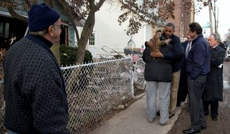 """President Obama hugs Staten Island resident Debbie Ingenito shortly after Superstorm Sandy's devastation in October 2012. Critics have decried his recent decision not to visit the Texas-Mexico border with Gov. Rick Perry, which the president dismissed as a mere political """"photo op"""" rather than a real solution to the ongoing crisis at the state's southern frontier. (associated press)"""