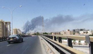 ** FILE ** Smoke rises from the direction of Tripoli airport in Tripoli, Libya, Sunday, July 13, 2014. Rival militias battled Sunday for the control of the international airport in Libya's capital, as gunfire and explosions echoed through the city and airlines canceled some international flights. (AP Photo)