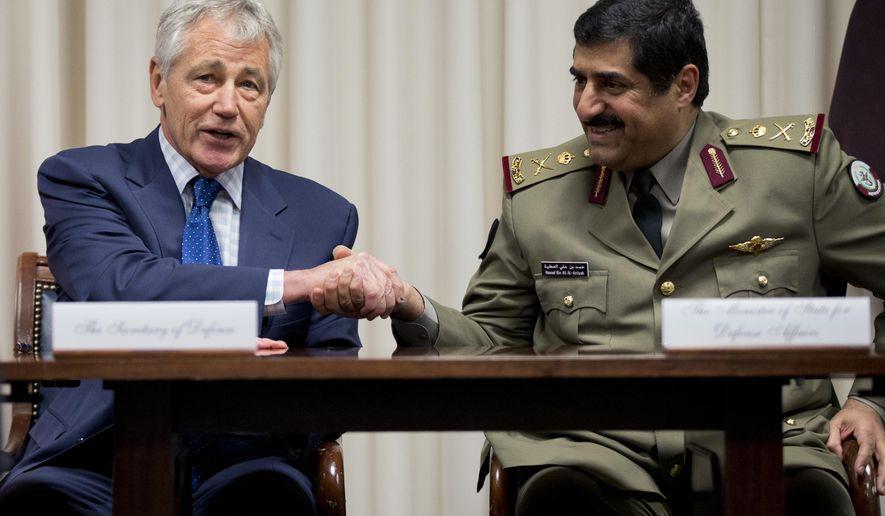Defense Secretary Chuck Hagel, left, shakes hands with Qatari Defense Minister Hamad bin Ali al-Attiyah, at the Pentagon, Monday, July 14, 2014, during a signing ceremony. (AP Photo/Manuel Balce Ceneta)