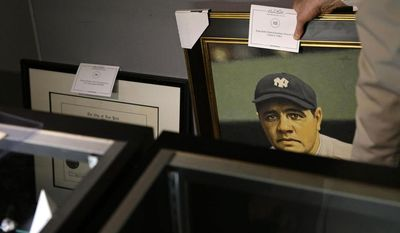 Goldin Auctions President Ken Goldin moves a portrait of Babe Ruth behind display cases, Wednesday, July 9, 2014, in Baltimore, during a media preview of sports memorabilia slated for auction to mark the 100th anniversary of his major league debut. (AP Photo/Patrick Semansky)