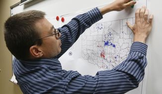 FILE - In this June 26, 2014 file photo, Austin Holland, research seismologist at the Oklahoma Geological Survey, hangs up a chart depicting earthquake activity at their offices at the University of Oklahoma in Norman, Okla. States where hydraulic fracturing is taking place have seen a surge in seismic activity, raising suspicions that the unconventional drilling method, especially the wells in which the industry disposes of its wastewater, could be to blame. (AP Photo/Sue Ogrocki, File)
