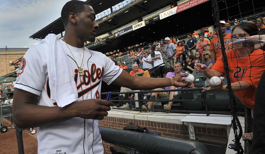 NBA basketball player for the Washington Wizards, John Wall signs autographs before a baseball game between the Baltimore Orioles and New York Yankees, Sunday, July 13, 2014, in Baltimore.(AP Photo/Gail Burton)
