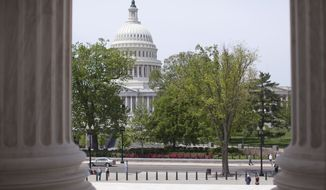 The U.S. Capitol building is seen through the columns on the steps of the Supreme Court in Washington, May 5, 2014. (Associated Press) ** FILE **