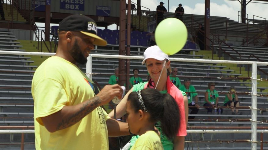 Bright was the mood of the day at the prison's annual family reunion. Volunteers with the Awana Lifeline ministry wore gray and lime-green T-shirts, and the inmates wore red, blue, yellow and dark green shirts.