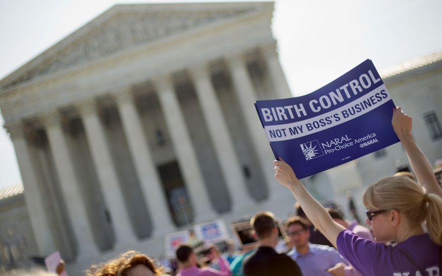 Demonstrators stand outside the Supreme Court on June 30, 2014, the day of the Hobby Lobby decision relieving businesses with religious objections of their obligation to pay for women's contraceptives. (Associated Press) **FILE**