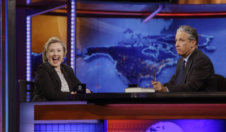 "Former U.S. Secretary of State Hillary Rodham Clinton reacts to host Jon Stewart during a taping of ""The Daily Show with Jon Stewart,"" Tuesday, July 15, 2014, in New York.  (AP Photo/Frank Franklin II)"