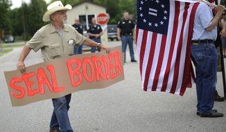 In this Monday, July 14, 2014, photo, Leszek Sulanowski, from Deford, Mich., holds up a sign calling for a secured border during a protest of a social services organization's proposal to house child immigrants from Central America in Vassar, Mich., amid escalating debate in about the plans. (AP Photo/Detroit News, Elizabeth Conley)