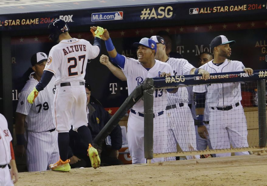 American League's Jose Altuve, of the Houston Astros, celebrates with teammates after scoring during the fifth inning of the MLB All-Star baseball game, Tuesday, July 15, 2014, in Minneapolis. (AP Photo/Paul Sancya)