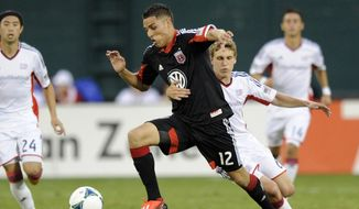 **FILE** New England Revolution midfielder Scott Caldwell, right, holds on to D.C. United's Luis Silva (12) during the second half of an MLS soccer game, Saturday, July 27, 2013, in Washington. The Revolution won 2-1. (AP Photo/Nick Wass)
