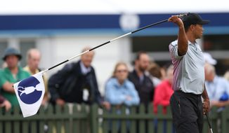 Tiger Woods of the US holds up the flag on the practice green ahead of the British Open Golf championship at the Royal Liverpool golf club, Hoylake, England, Wednesday July 16, 2014. The British Open Golf championship starts Thursday July 17. (AP Photo/Scott Heppell)