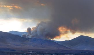 A wildfire fills the sky with smoke north and above Bordertown, Nev., Tuesday July 15, 2014.  Wildfires were also burning in Idaho, Oregon and California on Wednesday.  (AP Photo/The Reno Gazette-Journal, Marilyn Newton)  NO SALES; NEVADA APPEAL OUT; SOUTH RENO WEEKLY OUT