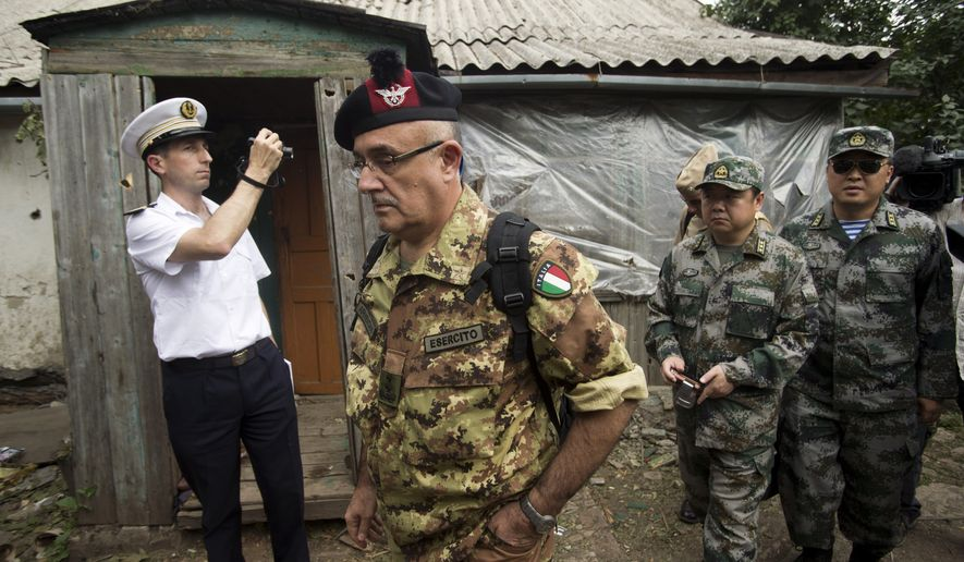 In this photo taken on Tuesday, July 15, 2014, a group of foreign defense attaches inspect at a yard and a house after shelling the Russian town of Donetsk, Rostov-on-Don region. (AP Photo/Pavel Golovkin)