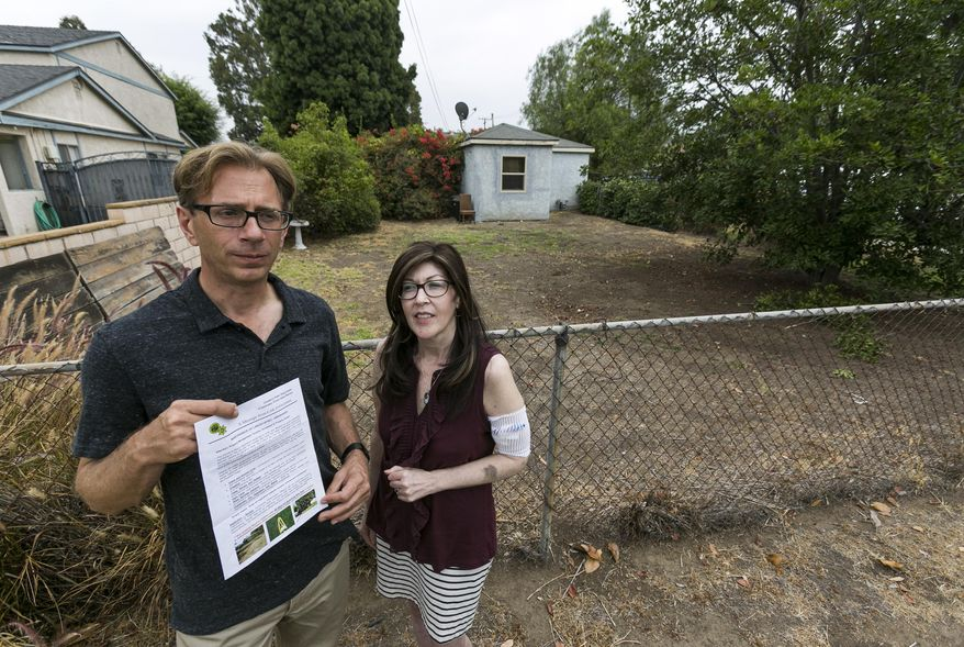 Michael Korte and his wife Laura Whitney, stand outside their home lawn in Glendora, Calif., Thursday, July 17, 2014. The Southern California couple who scaled back watering due to drought received a letter from the city of Glendora warning that they could face fines if they don't get their brown lawn green again. They are told if they don't revive the lawn they could be hit with up to $500 in fines and possible criminal action. City Manager Chris Jeffers says the couple has not been cited and called it a friendly letter prompted by a neighbor's complaint. (AP Photo/Damian Dovarganes)