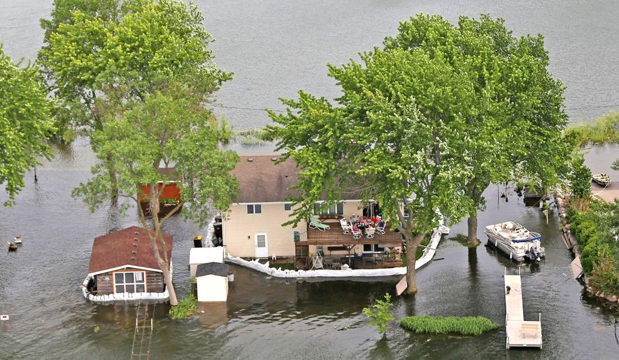 In a Friday June 27, 2014 photo, homes are surrounded  with sandbags in Prior Lake , Minn. for protection from flood waters by Prior Lake. Minnesota communities are trying to bounce back from last month's flooding as damage estimates continue to rise.  (AP Photo/The Star Tribune,Kyndell Harkness)  MANDATORY CREDIT; ST. PAUL PIONEER PRESS OUT; MAGS OUT; TWIN CITIES TV OUT