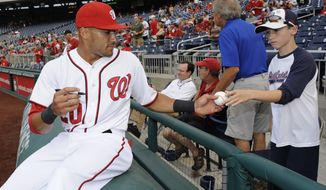 Washington Nationals shortstop Ian Desmond signs autographs for fans before a baseball game against the Miami Marlins, Tuesday, Aug. 27, 2013, in Washington. (AP Photo/Nick Wass)