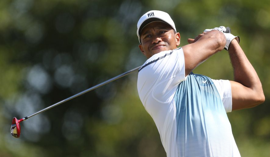 Tiger Woods of the US plays a shot off the 8th tee during the first day of the British Open Golf championship at the Royal Liverpool golf club, Hoylake, England, Thursday July 17, 2014. (AP Photo/Peter Morrison)