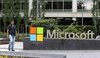 In this photo taken July 3, 2014, a worker walks past a Microsoft Corp. sign outside the Microsoft Visitor Center in Redmond, Wash. Microsoft on Thursday, July 17, 2014 announced it will lay off 18,000 workers over the next year. (AP Photo Ted S. Warren)