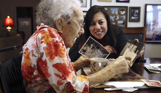 Lucy Coffey and Queta Marquez, Bexar County veterans service officer, go through pictures taken while Coffey was in Japan, July 21, 2014. (Associated Press) ** FILE **