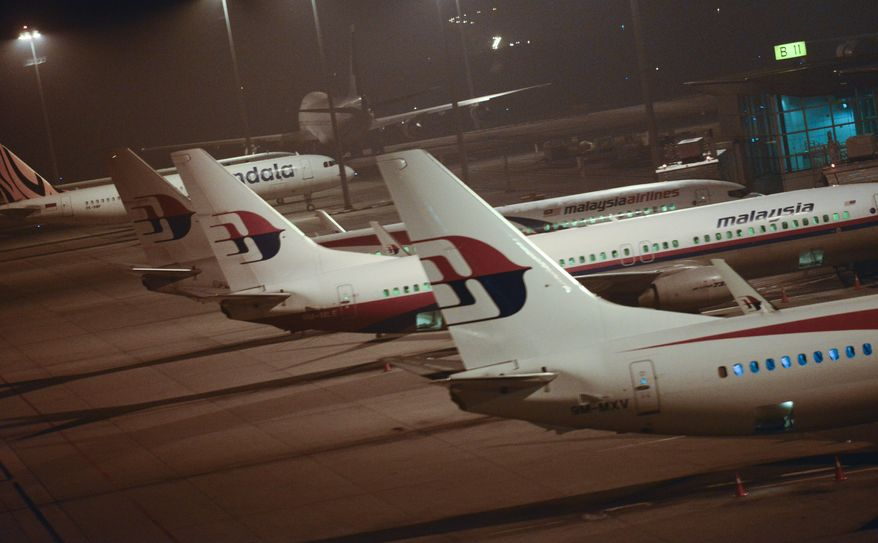 Malaysia Airlines planes are parked at Kuala Lumpur International Airport in Sepang, Malaysia, Thursday, July 18, 2013.  A Malaysia Airlines flight with nearly 300 people aboard crashed over eastern Ukraine near the Russian border on Thursday, the Ukraine government and a regional European aviation official reported, Thursday, and the Interfax news agency said it had been shot down.(AP Photo/Joshua Paul)