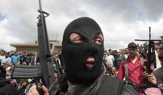 ** FILE ** A masked Lebanese Sunni gunman holds up his weapon in Akkar, north Lebanon. (AP Photo/Hussein Malla, File)