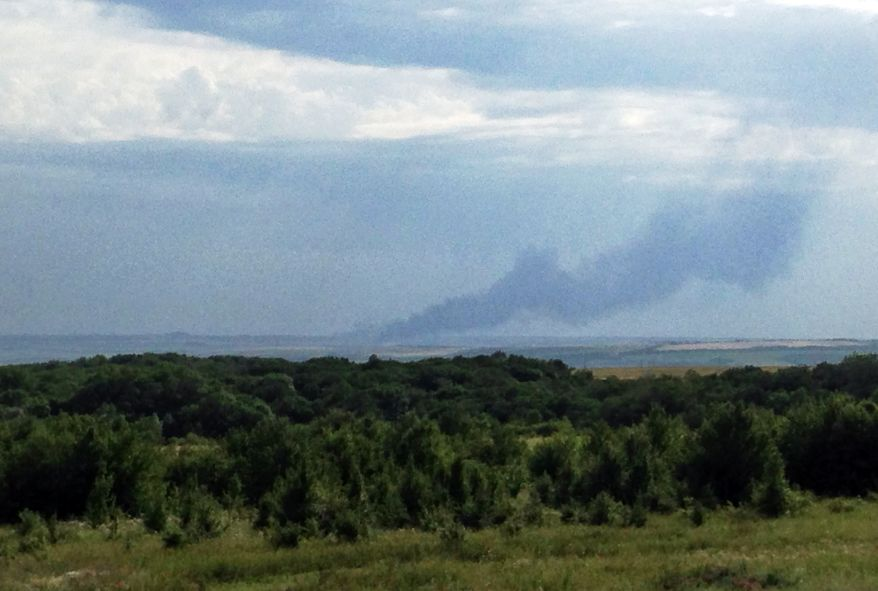 In this photo taken with a mobile phone provided by Andrei Kashtanov, smoke rises from where a Malaysia Airlines commercial flight plane crashed in eastern Ukraine, Thursday, July 17, 2014. Malaysia Airlines has said 295 people were aboard the flight from Amsterdam to Kuala Lumpur. (AP Photo/Andrei Kashtanov) MANDATORY CREDIT