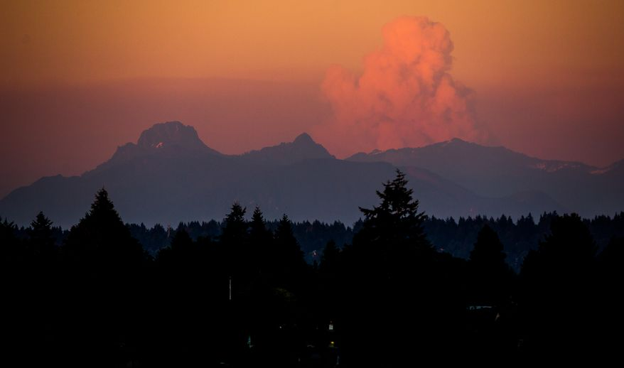 A large cloud rises over wildfires in Eastern Washington as seen from University District at sunset on Wednesday, July 16, 2014, in Seattle, Wash. Worsening wildfire activity has prompted the governor's offices in both Washington and Oregon to declare a state of emergency, a move that enables state officials to call up the National Guard. In Washington, that declaration covers 30 eastern Washington counties. (AP Photo/seattlepi.com, Jordan Stead)