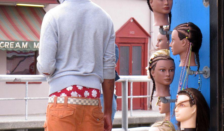 **FILE** A young man wears saggy pants on the Wildwood, N.J. boardwalk on June 6, 2013. (Associated Press)