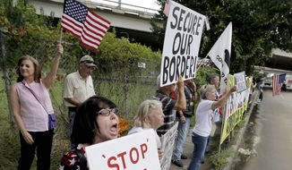 Barbie Miller, left, yells as she joins demonstrators outside the Mexican Consulate Friday, July 18, 2014, in Houston.   Prospects for action on the U.S.-Mexico border crisis faded Thursday as lawmakers traded accusations rather than solutions, raising chances that Congress will go into its summer recess without doing anything about the tens of thousands of migrant children streaming into South Texas. (AP Photo/David J. Phillip)