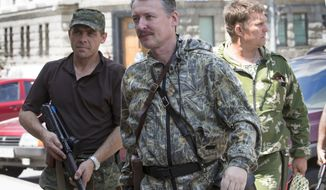"FILE - In this Friday, July 11, 2014 file photo, Igor Girkin  also known as Igor Strelkov, a pro-Russian commander, center, arrives for the wedding of platoon commander Arsen Pavlov and Elena Kolenkina in the city of Donetsk, eastern Ukraine. A top pro-Russia rebel commander in eastern Ukraine has given a version of events surrounding the Malaysian jetliner crash _ suggesting many of the victims may have died days before the plane took off. The pro-rebel website Russkaya Vesna on Friday, July 18, 2014,  quoted Igor Girkin as saying he was told by people at the crash site that ""a significant number of the bodies weren't fresh,"" adding that he was told they were drained of blood and reeked of decomposition.(AP Photo/Dmitry Lovetsky, File)"