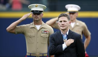 "Medal of Honor recipient retired Marine Cpl. William ""Kyle"" Carpenter stands with fellow Marines as the National Anthem is played before a baseball game between the Atlanta Braves and Philadelphia Phillies  in Atlanta, Saturday, July 19, 2014. Carpenter received the Medal of Honor for his courageous actions while serving in Afghanistan. (AP Photo/John Bazemore)"