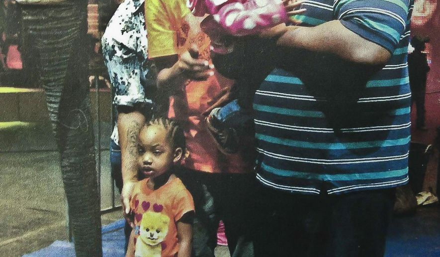 In this undated family photo provided by the National Action Network, Saturday, July 19, 2014, Eric Garner, right, poses with his children during during a family outing. Garner was confronted by police trying to arrest him on suspicion of selling untaxed, loose cigarettes on a Staten Island sidewalk, authorities said. The 6-foot-3, 350-pound Garner became irate, denying the charges and refusing to be handcuffed before one of the officers placed him in what Police Commissioner William Bratton said appeared to be a chokehold, according to partial video of the encounter obtained by the New York Daily News. (AP Photo/Family photo via National Action Network)